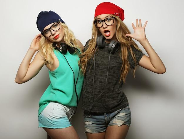 Ritratto di due migliori amiche ragazze hipster che indossano abiti eleganti e luminosi, cappelli, pantaloncini di jeans e occhiali, impazziscono e si divertono insieme. giovani e bellezza.