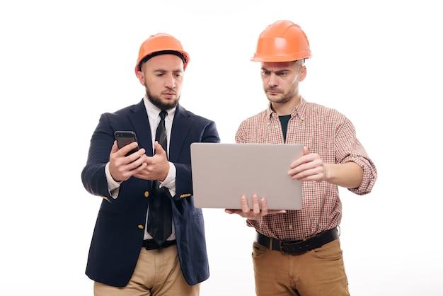 Ritratto di due costruttori in caschi protettivi arancioni in piedi su sfondo bianco isolato e guardando il display del laptop. discuti il progetto di costruzione