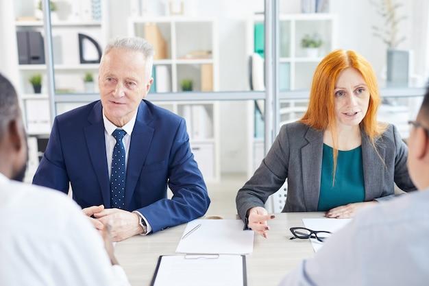 Un ritratto di due persone di affari che intervistano i candidati per la posizione di lavoro in un ufficio moderno