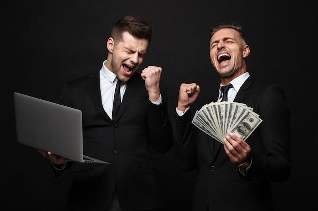 Ritratto di due uomini d'affari vestiti con abiti formali che celebrano mentre tengono in mano un laptop e banconote in denaro isolate su un muro nero
