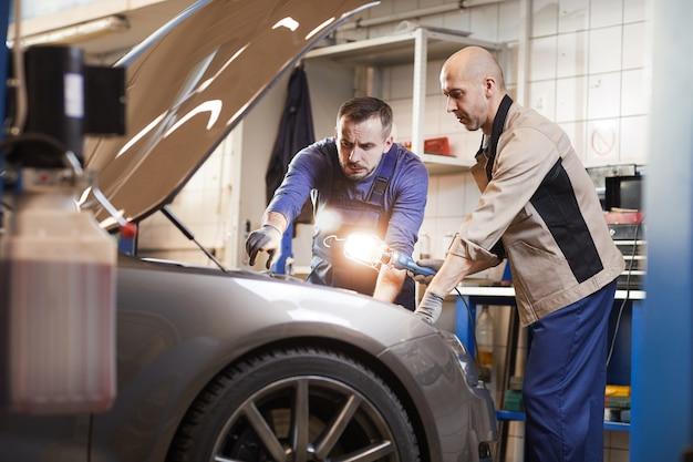 Ritratto di due meccanici di automobili guardando sotto il cofano della macchina in officina di riparazione auto, copia dello spazio