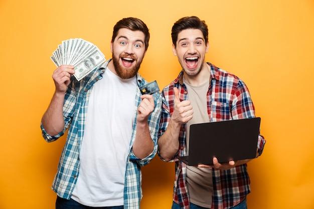 Ritratto di due giovani allegri che tengono computer portatile
