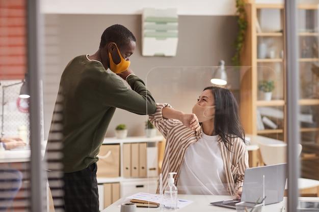 Ritratto di due colleghi che toccano i gomiti come saluto senza contatto in ufficio mentre indossano maschere