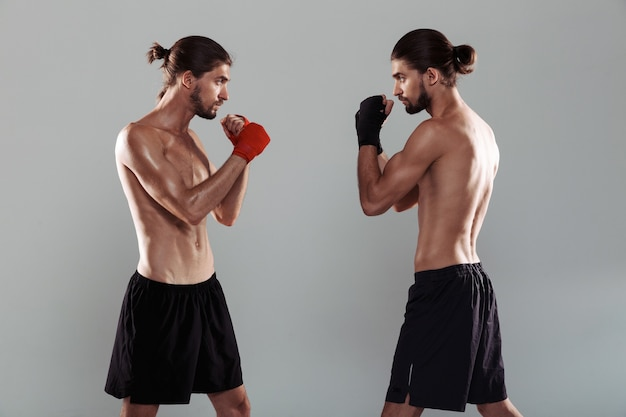 Ritratto di due fratelli gemelli senza camicia muscolosi fiduciosi