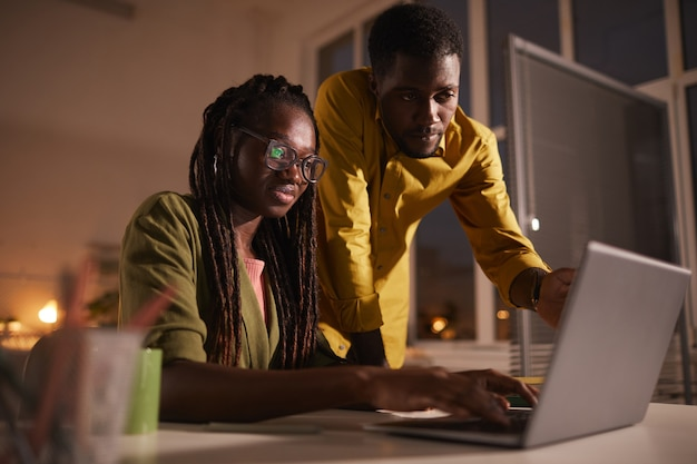 Ritratto di due persone afro-americane contemporanee guardando lo schermo del laptop mentre si lavora fino a tardi in ufficio fioco