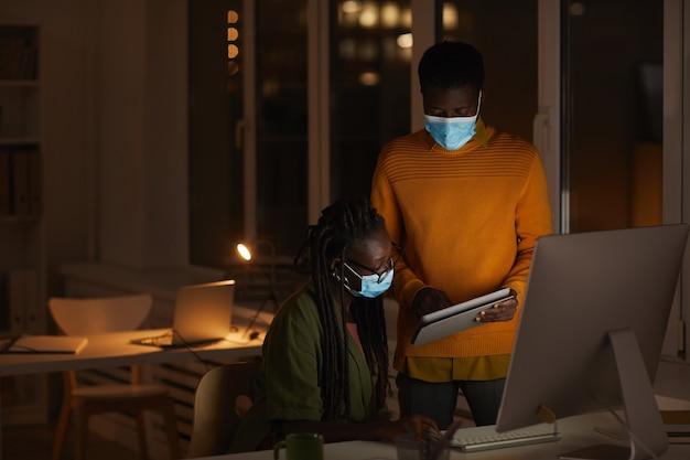 Ritratto di due persone afro-americane contemporanee che indossano maschere in ufficio mentre si lavora fino a tardi in ufficio buio, copia spazio