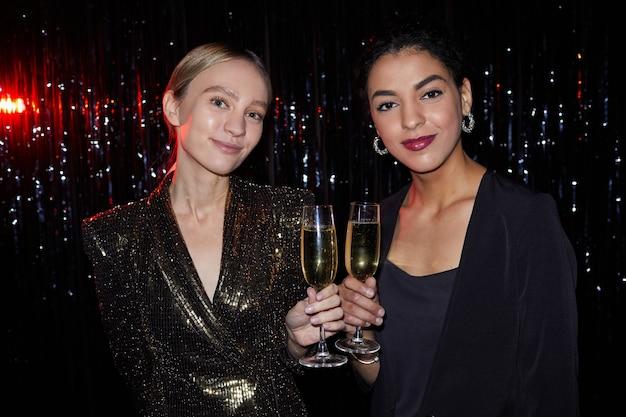 Ritratto di due giovani donne eleganti che tengono bicchieri di champagne e sorridono alla telecamera mentre posa su sfondo scintillante alla festa, girato con flash