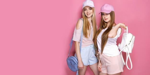Un ritratto di due ragazze allegre eccitate si è vestito nei sacchetti variopinti luminosi della holding dell'estate dei vestiti isolati.