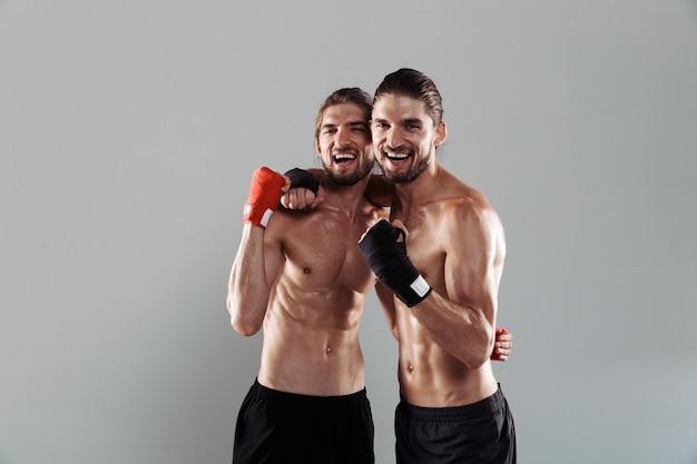 Ritratto di due fratelli gemelli senza camicia muscolosi eccitati