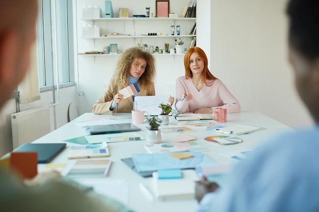 Ritratto di due designer di sesso femminile seduto di fronte a due uomini mentre discute del progetto creativo, copia dello spazio