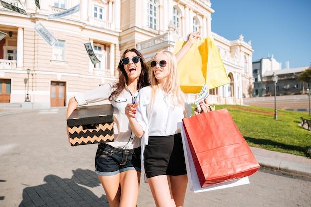 Ritratto di due amiche che fanno shopping insieme e camminano con i sacchetti colorati