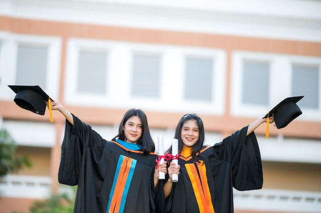 Ritratto due donne laureate, laureate, che tengono felicemente il cappello davanti.