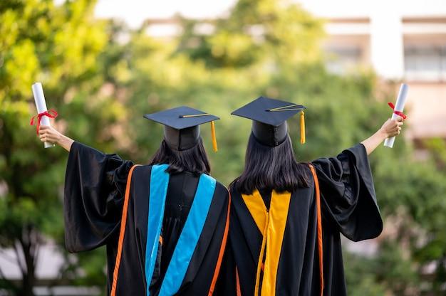 Ritratto due donne laureate, laureate in possesso di un diploma e sono felici