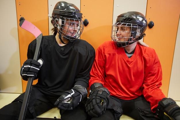 Un ritratto di due giocatori di hockey femminili che sorridono a vicenda nello spogliatoio