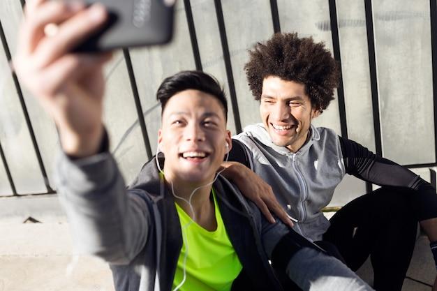 Ritratto di due giovani uomini in forma e sportivi che utilizzano il telefono cellulare in città.