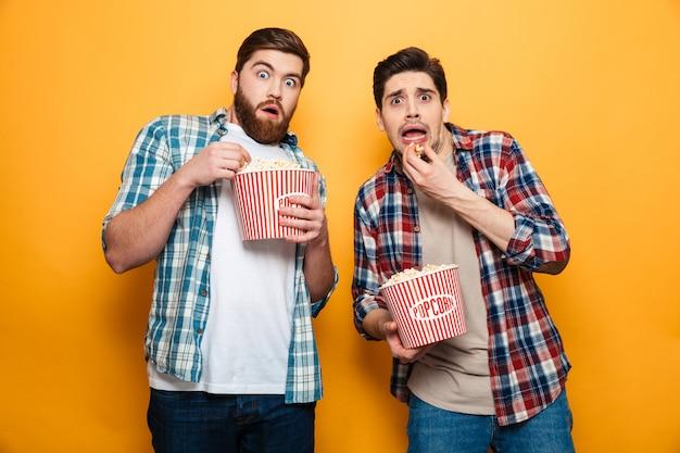 Ritratto di due giovani spaventati che mangiano popcorn