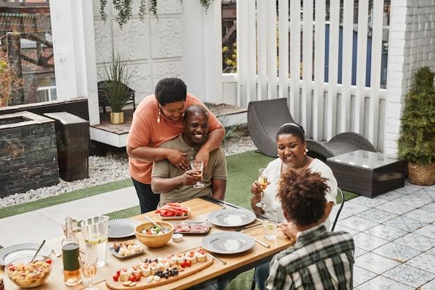 Ritratto di una famiglia afroamericana di due generazioni che si gode la cena insieme a una coppia anziana che si abbraccia...