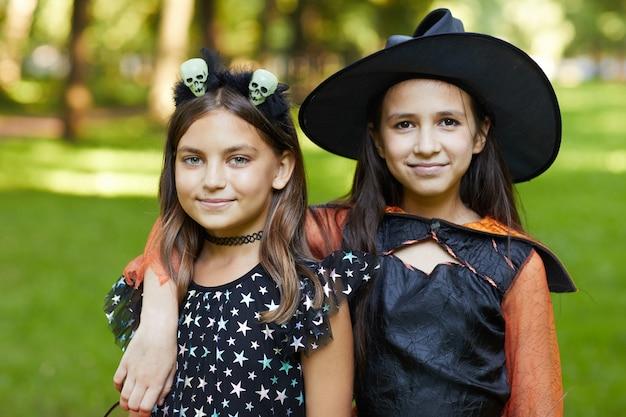 Ritratto di due ragazze in costumi di halloween che sorride alla macchina fotografica mentre levandosi in piedi all'aperto