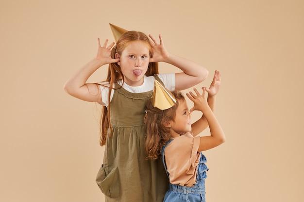 Ritratto di due ragazze che fanno facce buffe mentre posa sul beige
