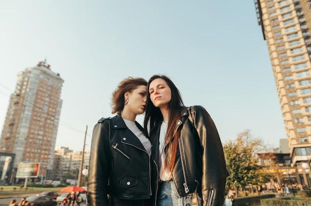 Ritratto di due ragazze in abiti da strada in piedi sull'erba sul paesaggio urbano
