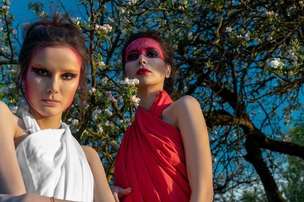 Ritratto di due ragazze con trucco creativo sullo sfondo di un albero di mele in fiore