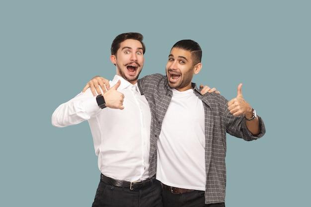 Ritratto di due bei amici barbuti o partner felici che si abbracciano e guardano la telecamera con faccia stupita soddisfatta e pollice in alto. studio indoor girato, isolato su sfondo azzurro.
