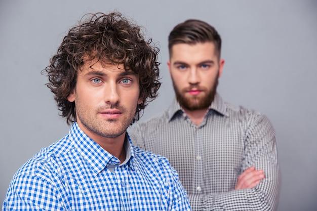 Ritratto di due bei uomini d'affari in piedi con le braccia conserte sul muro grigio