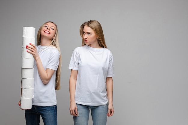 Ritratto di due belle ragazze con lunghi capelli biondi, uno di loro tiene molta carta igienica e l'altro è offeso isolato