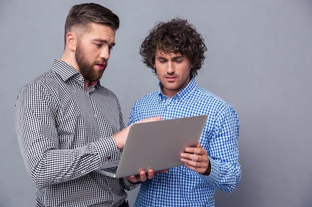 Ritratto di due uomini belli che utilizzano computer portatile sul muro grigio