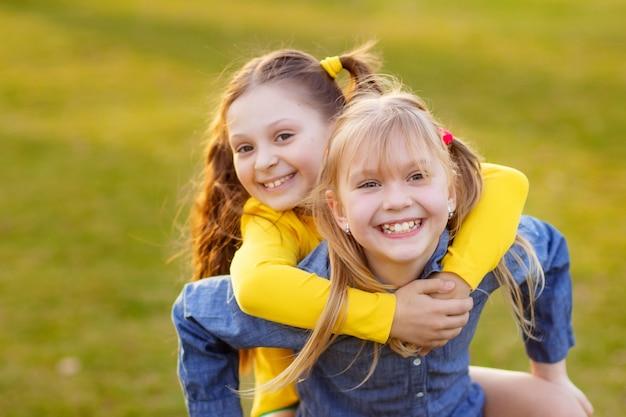 Ritratto di due ragazze carine felici all'aperto nel parco, bambini che si divertono