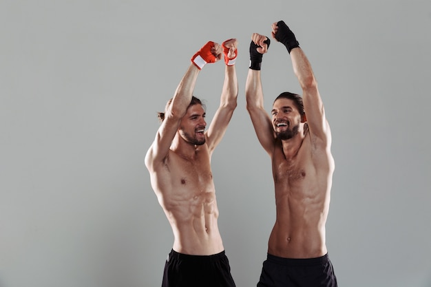 Ritratto di due fratelli gemelli senza camicia muscolosi felici