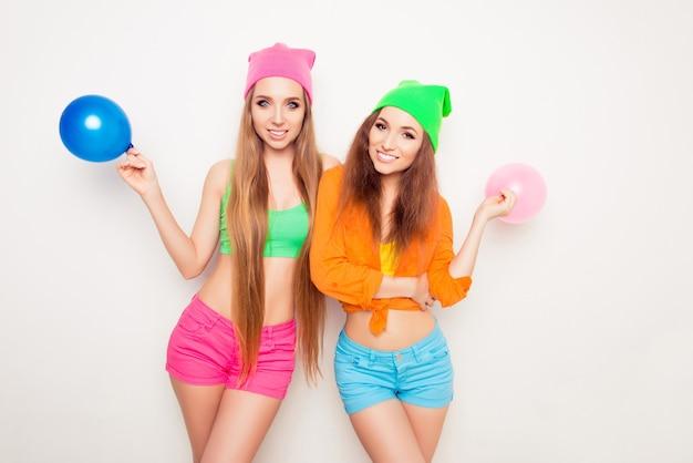 Un ritratto di due giovani sorelle alla moda felici che tengono i palloni