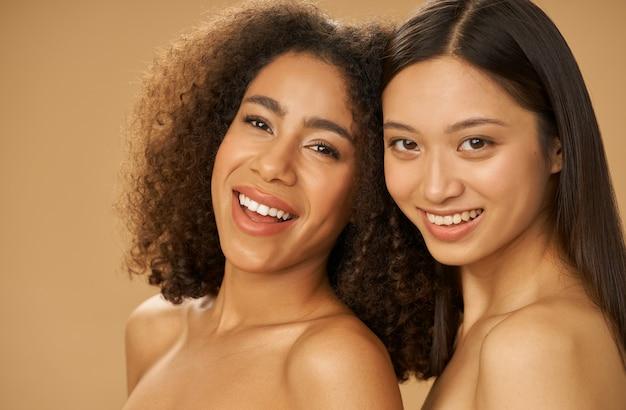Ritratto di due giovani donne gioiose e attraenti di razza mista con un sorriso perfetto in posa per la macchina fotografica