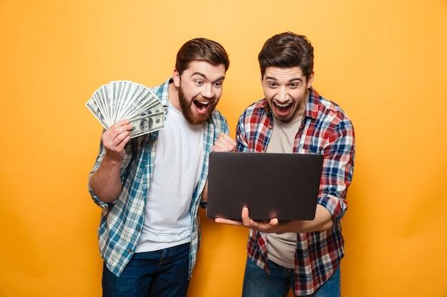 Ritratto di due giovani allegri che per mezzo del computer portatile Foto Premium