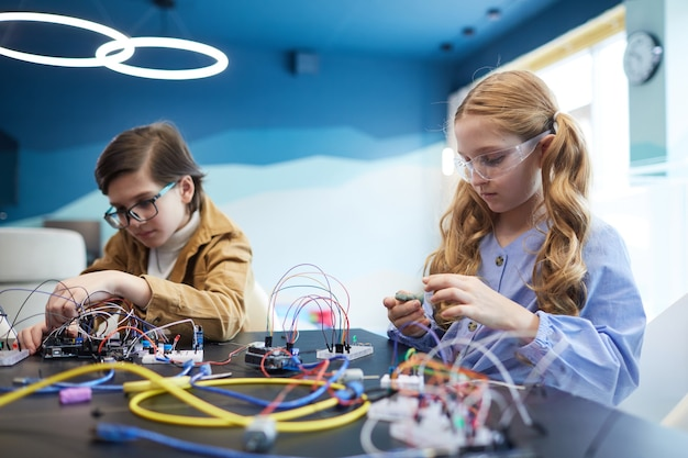 Ritratto di due bambini che costruiscono robot e sperimentano circuiti elettrici in classe di ingegneria a scuola