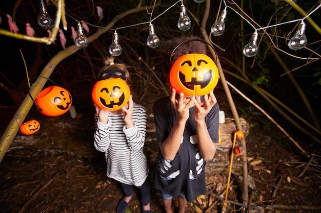 Un ritratto di due bambini che tengono le zucche del giocattolo davanti ai loro volti mentre levandosi in piedi nel buio all'aperto alla festa di halloween