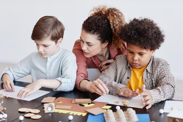 Ritratto di due bambini che realizzano modelli di cartone durante la lezione di arte e artigianato a scuola con insegnante femminile