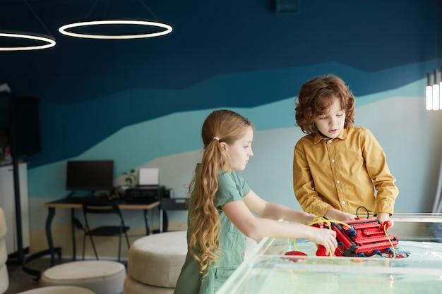 Ritratto di due bambini che mettono la barca robo in acqua mentre sperimentano la tecnologia nel laboratorio di robotica a scuola, copia spazio
