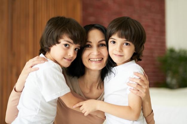 Ritratto di due bambini latini piccoli gemelli che sorridono alla telecamera e abbracciano la loro mamma