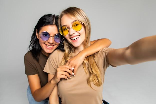 Ritratto di due donne adorabili in occhiali da sole in piedi e facendo un selfie isolato su un muro bianco