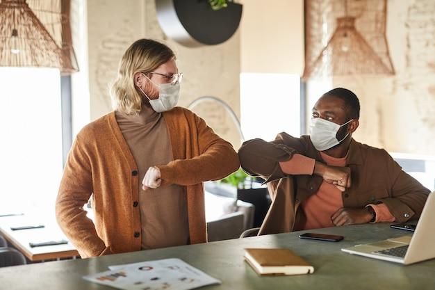 Ritratto di due uomini che indossano maschere e urtano i gomiti durante il saluto senza contatto in un bar o in ufficio, concetto covid, spazio copia