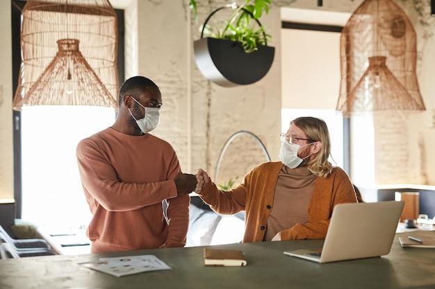 Ritratto di due uomini che indossano maschere e battono i pugni durante il saluto senza contatto in un bar o in ufficio, concetto covid, spazio copia