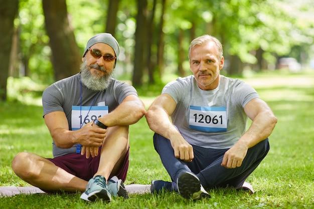 Ritratto di due moderni sportivi senior che prendono parte alla maratona estiva che si siede sull'erba nel parco cittadino che guarda l'obbiettivo
