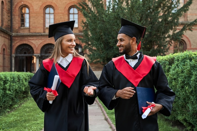 Ritratto di due laureati multinazionali che parlano nel campus universitario in abiti di laurea.