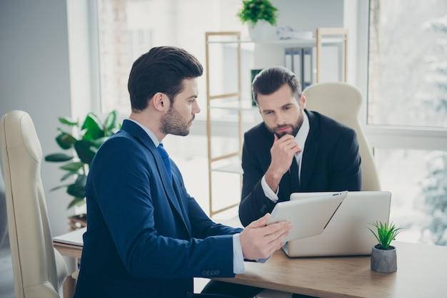 Ritratto di due uomini di classe belli attraenti che si incontrano per discutere della strategia del piano finanziario reddito aumento della crescita del profitto nella stazione del posto di lavoro interno bianco chiaro al chiuso