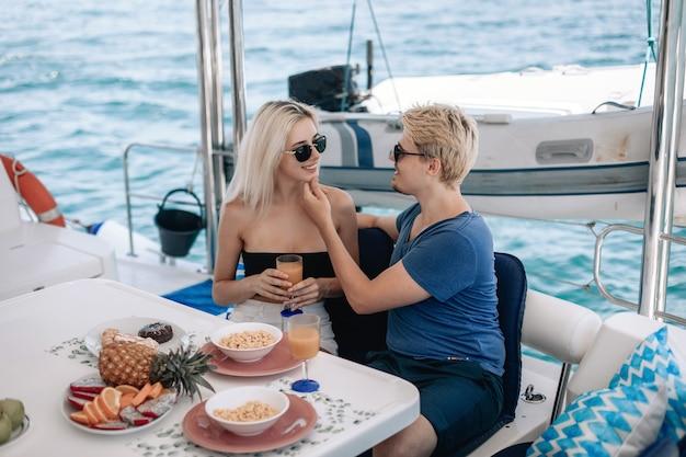 Ritratto di due persone innamorate trascorrere del tempo insieme e rilassarsi, navigare su uno yacht e cenare