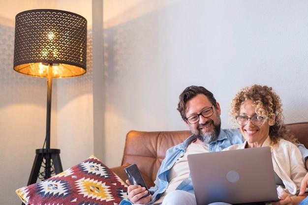 Ritratto di due persone, uomo e donna, che si divertono con la tecnologia di connessione toether con laptop e telefono che sorridono e guardano il computer