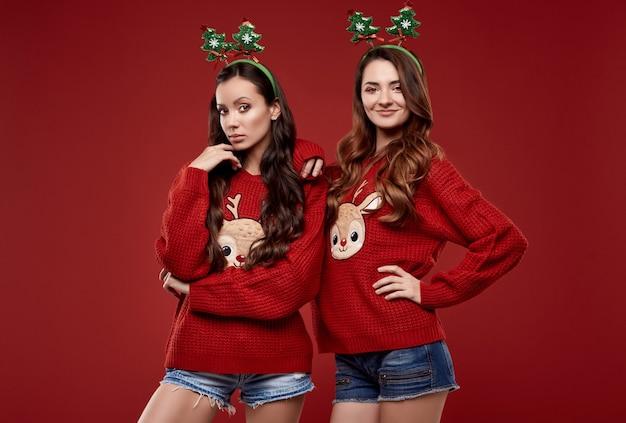Ritratto di due migliori amici piuttosto pazzi in maglione invernale accogliente di moda con attributi di natale in posa sulla parete rossa