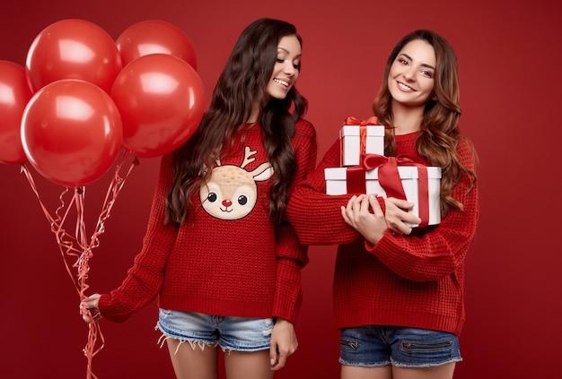Ritratto di due gemelli di amici migliori piuttosto pazzi in maglione invernale accogliente di moda con palloncini festa e scatole regalo in posa