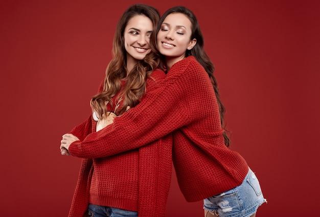 Ritratto di due gemelli migliori amici sorelle piuttosto pazze in posa accogliente maglione di inverno di modo
